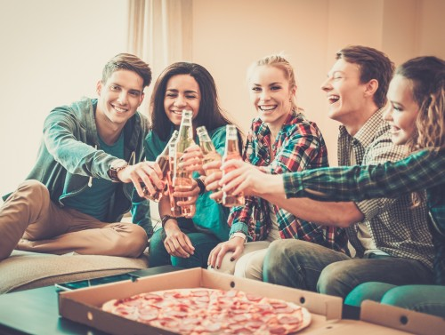 Group of young multi-ethnic friends with pizza and bottles of dr